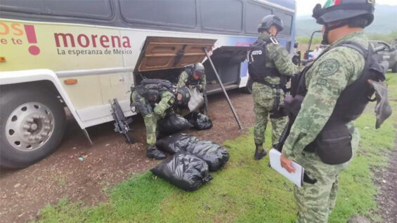 Soldiers remove meth from the cargo bay of a bus bearing the Morena logo.